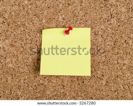 Cork-board with yellow memo note and pin