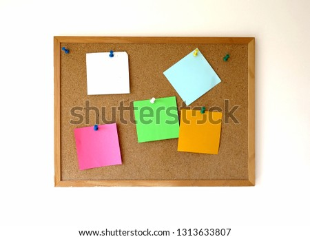 Cork bulletin board with empty pinned paper reminders on a white wall
