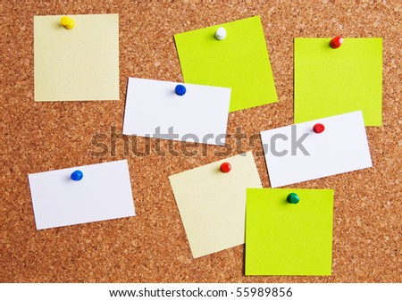 Cork bulletin board with notes and business cards.