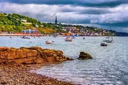 Cork Harbour in Ireland with sailboats and boats and town of Cobh skyline