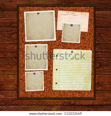 Cork notice board on a wooden background with blank photos and notepaper for content.