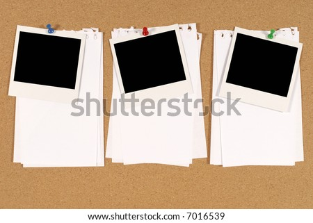 cork notice or bulletin board with three blank instant camera photo prints and several sheets of