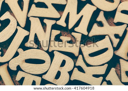 Corkboard covered with multiple wooden letters as a background composition. #417604918