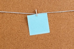 Corkboard with blue color stickers fixed by a pin. Square shaped sheets stuck on a billboard by colored thumbtacks. Notice board with empty reminder note.