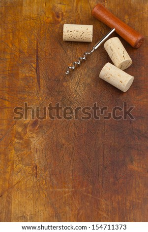 Corkscrew and wine corks on wooden background