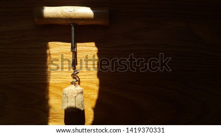 corkscrew, bottle opener, at the edge of the corkscrew wine cork, on a wooden background, space for copying text #1419370331