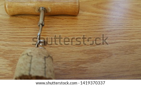 corkscrew, bottle opener, at the edge of the corkscrew wine cork, on a wooden background, space for copying text #1419370337