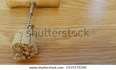 corkscrew, bottle opener, at the edge of the corkscrew wine cork, on a wooden background, space for copying text #1419370340