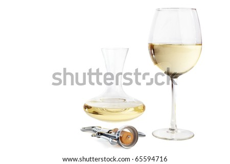 Corkscrew in front of a white wine glass and a carafe