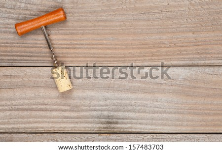 Corkscrew with wine cork on wooden planks