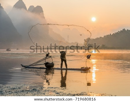 Cormorant fisherman throws a net with ancient traditional chinese bamboo boats at sunrise - Xingping, China   #719680816