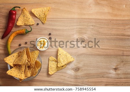 Corn chips in the jar. Traditional snack for beer Mexican nachos. Nachos with spices and pepper on wooden table. #758945554