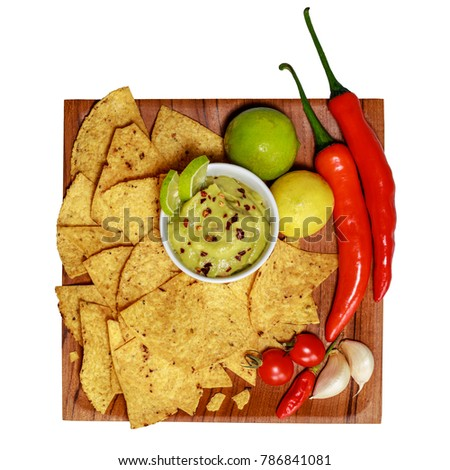 Corn chips nachos and guacamole in a white ceramic bowl on a wooden square plate. Garlic cloves, limes, cherry tomatoes, chilly peppers. White background. Top view. Isolated. Square image. #786841081