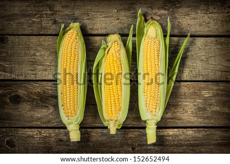 Corn cobs on vintage wood background