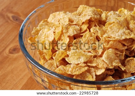 Corn flake cereal in glass bowl on wood background.  Macro with shallow dof.