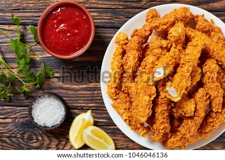 corn flakes breaded deep fried chicken crispy breast strips on white plate, on old rustic  wooden table with tomato sauce and lemon slices, easy recipe for outdoor picnic or party, close-up