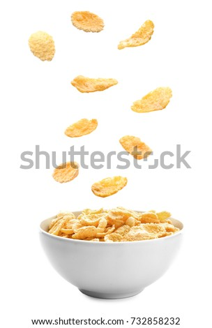 Corn flakes falling into bowl on white background #732858232