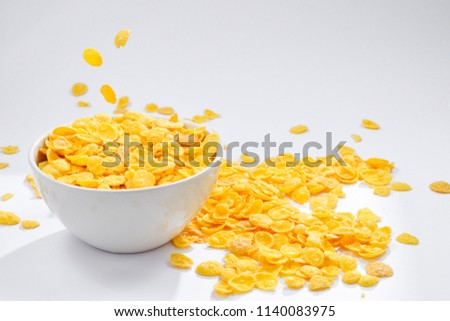 Corn flakes falling to the white bowl. Motion. Copyspace. #1140083975