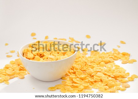 Corn flakes falling to the white bowl. Motion. Copyspace. #1194750382
