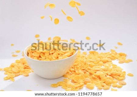Corn flakes falling to the white bowl. Motion. Copyspace. #1194778657