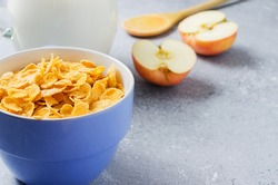 Corn flakes in a blue Cup and Apple slices. Useful Breakfast in the morning. Copy space