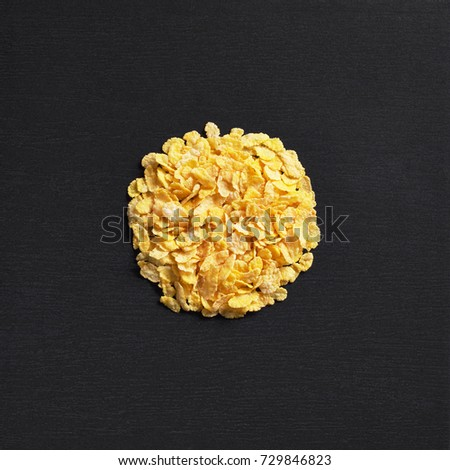 Corn flakes on black stone background, top view. Space for text #729846823