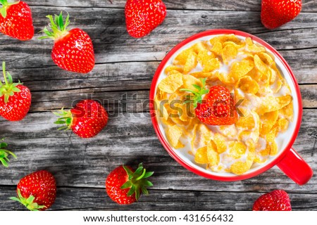 corn flakes with milk and strawberry in a red cup on an old rustic table, close-up, top view  #431656432