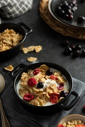 Corn flakes with strawberry and blueberry in black bowls over dark background