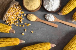 Corn flour and starch in wooden bowl and spoon with dried corn groats, kernels on rustic table. corn ingredients concept