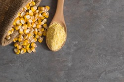 Corn flour in wooden bowl and spoon with dried corn groats, kernels on rustic table. corn ingredients concept