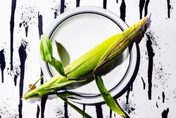 Corn in husk on abstract modern paint drips and spatters background concept