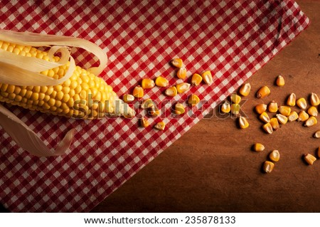 corn maize lying lying on red dish-cloth in rustic style