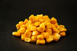 Corn. Pile of yellow corn kernels over the black background. Pile canned sweet corn kernels.