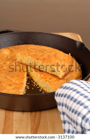 Cornbread in a cast iron skillet with piece cut out vertical view