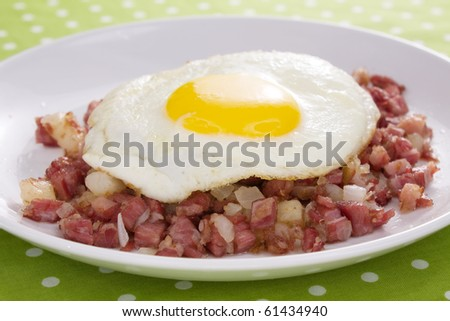 Corned beef fried with potatoes and onions, topped with a sunny side up fried egg.