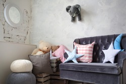 corner in the nursery. sofa with pillows in the form of stars and months. boxes of toys, Teddy bear. toy stuffed elephant on the wall