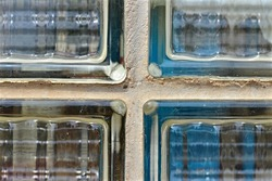 Corner joint of four glass tiles / luxfers. Detail on an old window composed of glass tiles.