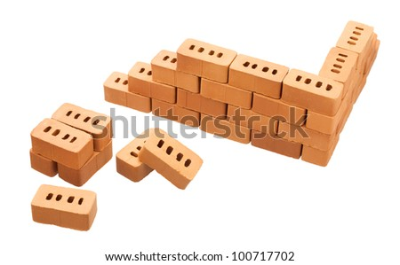 Corner of a brick wall and heap of bricks isolated on white background
