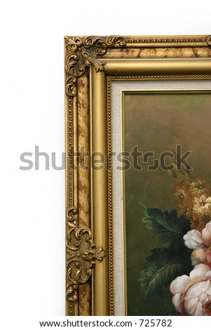 Corner of a gold painted ornate picture frame of an oil painting of flowers