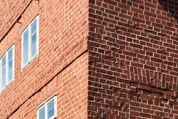 Corner of a house made of red bricks with one wall in sunshine and the other in shadow, abstract