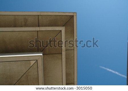 corner of a roof, blue sky and a white trail from an airplane