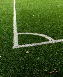 Corner of a soccer field in an stadium. Markings Of A Football Field. Playing sports field, corner kick. Autumn leaves are lying on the grass. Middle position.