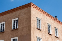 Corner of an adobe building with white windows