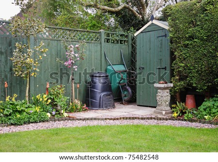 Corner of an English back Garden with shed, compost bin and wheelbarrow