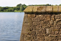 Corner of Ancient Fortification beside Blue Waters of Lake on Sunny Day