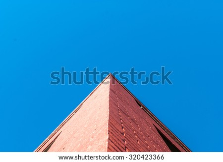 Corner of building. Red brick building with blue sky background. Abstract art architecture. Minimal design and art. Symmetrical design. Architectural design.