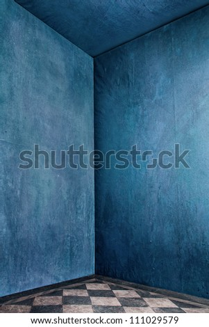 corner of grunge room with blue old walls and tiled floor