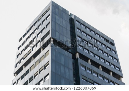 Corner of modern high-rise office building with dark facade of concrete viewed from low angle against grey sky