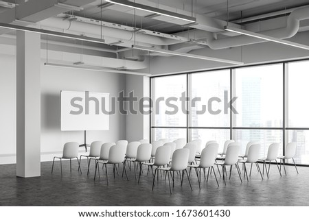 Corner of modern industrial style office lecture hall with white walls, concrete floor, rows of white chairs and mock up projection screen. Concept of presentation and education. 3d rendering