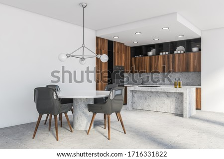 Corner of modern kitchen with white walls, wooden countertops and cupboards, island with built in cooker and round dining table with gray chairs. 3d rendering